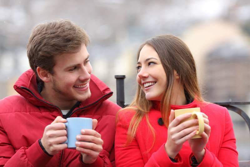 Couple parlant assis sur un banc avec un café
