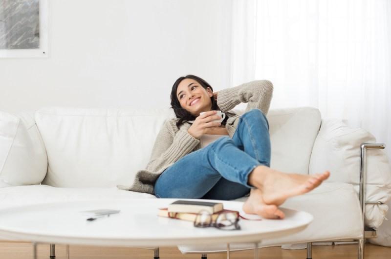 femme souriante assise sur un canapé en buvant du thé