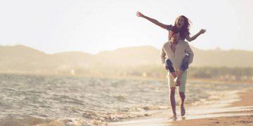 couples heureux piggybacking sur la plage