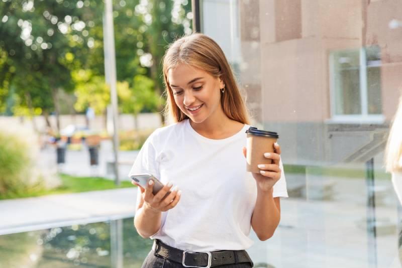 jeune fille tapant sur son téléphone à l'extérieur