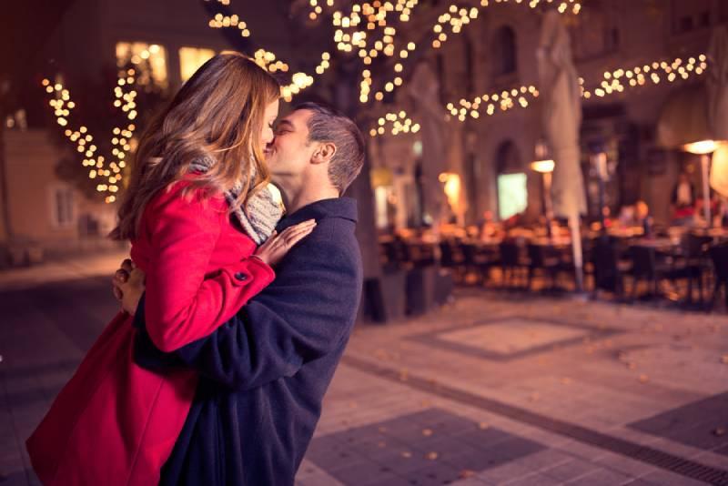 Un jeune couple affectueux s'embrasse en plein air dans la rue