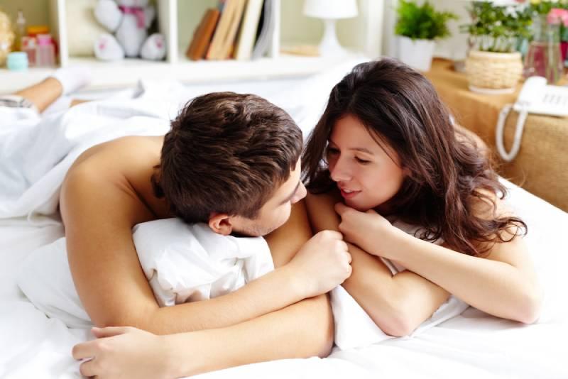 Un jeune couple parle dans son lit le matin