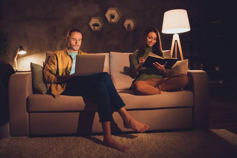 Un joyeux couple assis sur un divan passe du temps